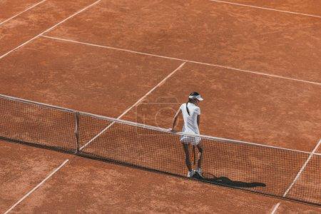Photo pour Vue grand angle de la femme se détendre sur le court de tennis et se pencher en arrière sur le filet - image libre de droit