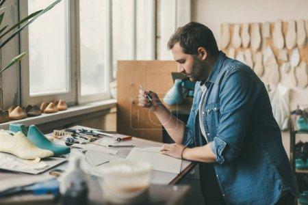 Photo pour Concentré de jeune cordonnier sur lieu de travail dans la boutique de cordonnier - image libre de droit