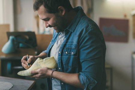 Photo pour Souriante jeune cordonnier travaille avec pied échantillon - image libre de droit
