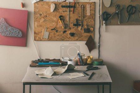 Photo pour Table avec des échantillons de cuir et de différents outils avec des ciseaux à l'atelier de cordonnier - image libre de droit
