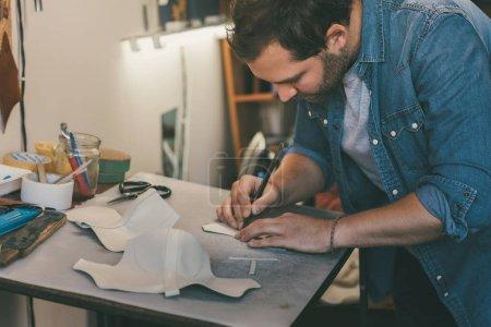 Photo pour Cuir de traçage jeune cordonnier pour chaussures sur lieu de travail - image libre de droit