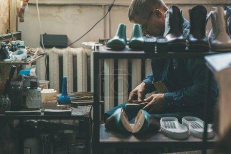 Photo pour Cordonnier expérimenté créant des chaussures en atelier - image libre de droit