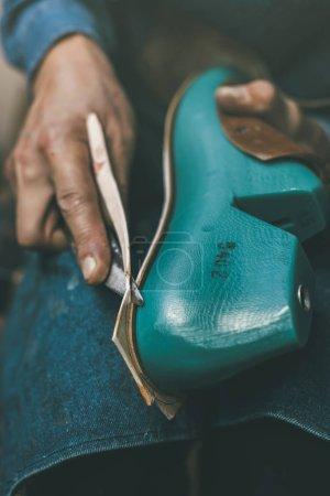 Photo pour Recadrée tir du matériau de coupe cordonnier avec couteau pour la taille de l'échantillon de pied - image libre de droit