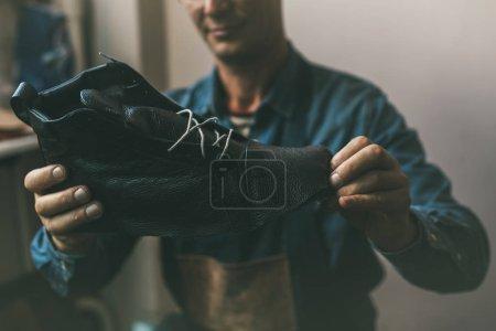 Photo pour Gros plan de cordonnier en regardant botte en cuir inachevé - image libre de droit