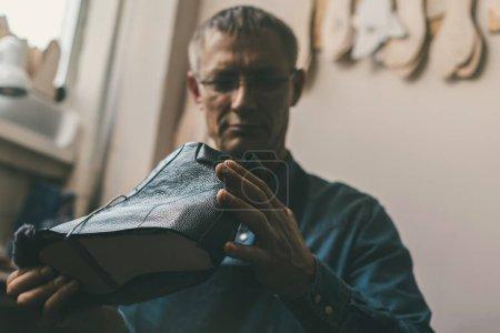 Photo pour Mature cordonnier regardant botte en cuir inachevé - image libre de droit