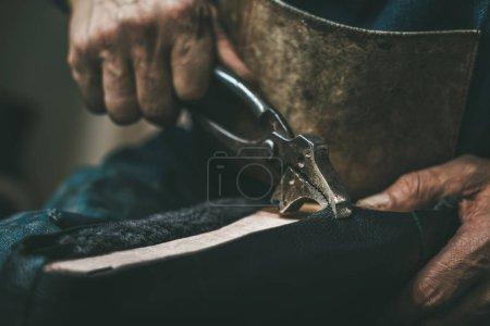 Photo pour Recadrée tir de mutualisation cuir chaussure avec une pince de cordonnier - image libre de droit