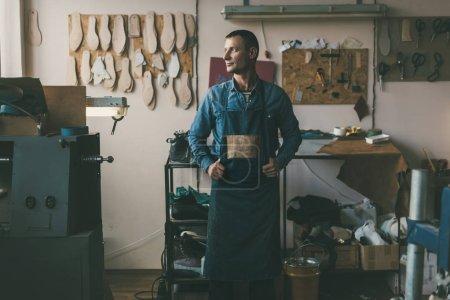 Photo pour Beau cordonnier adulte en vêtements de travail et tablier en atelier - image libre de droit