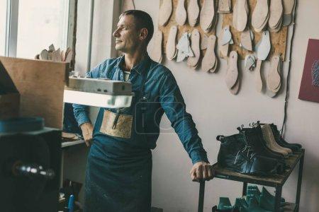 Photo pour Gentil cordonnier en vêtements de travail et tablier en atelier - image libre de droit
