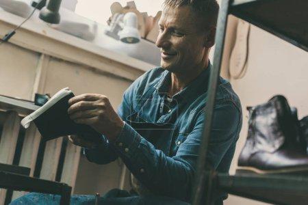Photo pour Souriant cordonnier adulte travaillant sur la paire de chaussures en atelier - image libre de droit