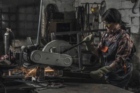 Photo pour Female soudeur dans googles protecteur à l'aide de torche de soudage en atelier - image libre de droit