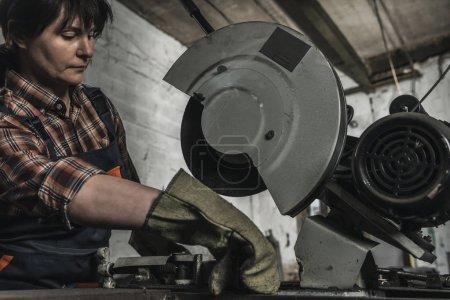 Photo pour Concentré de soudeur femelle à l'aide de torche de soudage en atelier - image libre de droit
