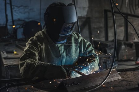 Photo pour Ouvrier en casque de protection avec torche travaillant dans l'atelier de soudage - image libre de droit