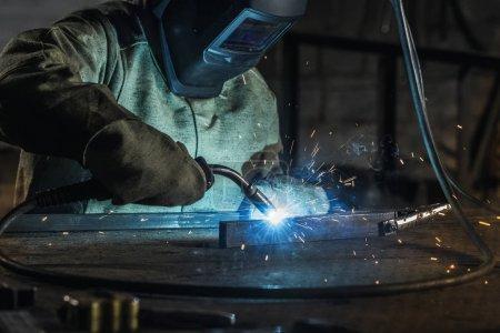 ouvrier en casque de protection avec torche de soudage travaillant en atelier