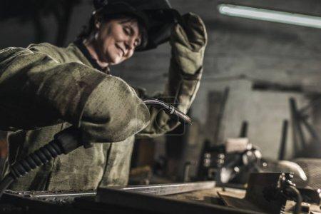 Photo pour Mise au point sélective de soudeur femelle dans les vêtements de protection travail travaillant dans l'atelier - image libre de droit