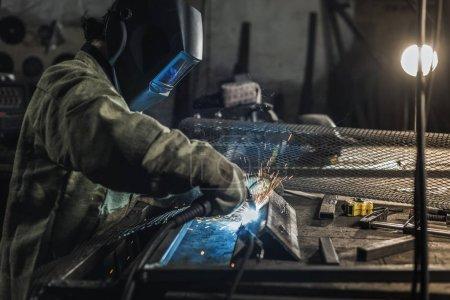 Photo pour Vue latérale du soudeur en vêtements de travail protecteurs travaillant avec torche dans l'atelier de soudage - image libre de droit