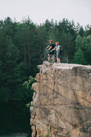 side view of young trial bikers standing on rocky cliff with blurred pine forest on background