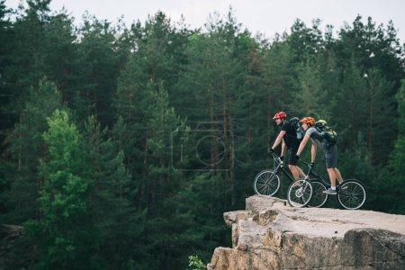 side view of young trial bikers standing on rocky cliff with blurred pine forest on background and looking at side