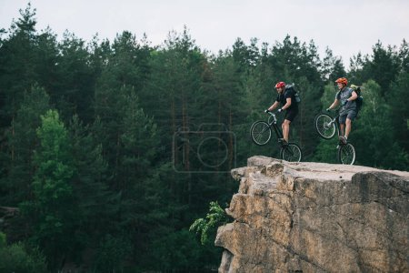 side view of young trial bikers with backpacks standing on back wheels on rocky cliff with blurred pine forest on background