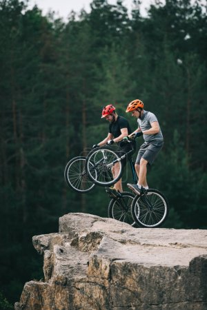 risky trial bikers standing on back wheels on rocky cliff with blurred pine forest on background