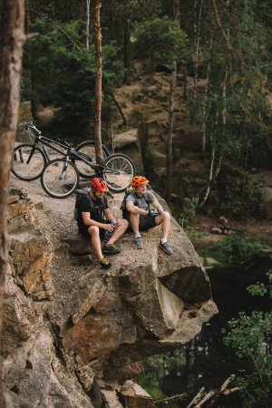 high angle view of happy young trial bikers relaxing on rocky cliff after ride
