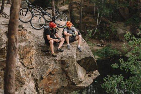 Photo pour Vue en angle élevé de jeunes cyclistes actifs qui se détendent sur une falaise rocheuse après une randonnée - image libre de droit