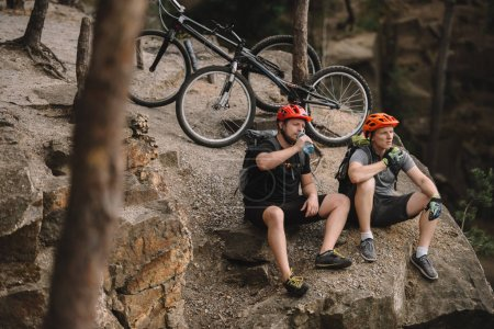 high angle view of young trial bikers relaxing on rocky cliff after ride and having meal