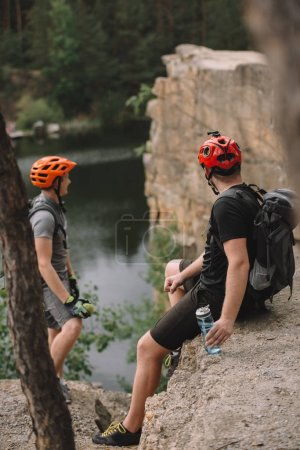 young tourists in helmets relaxing on rocky cliff after ride