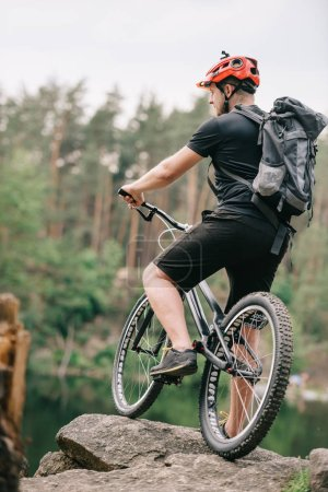 trial biker standing with bicycle on rock outdoors