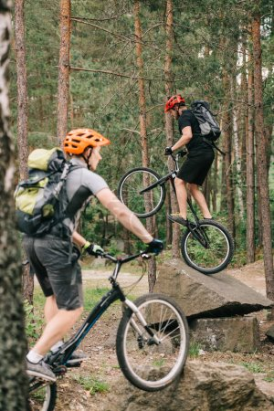 young trial bikers having fun in pine forest
