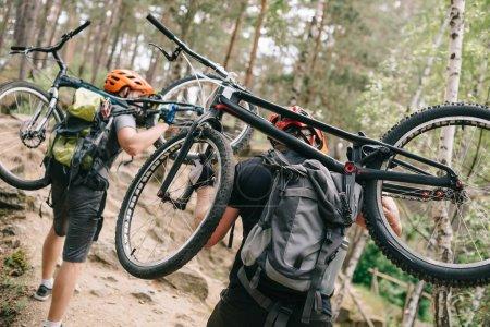 Rückansicht junger Trial-Biker mit Fahrrädern auf dem Rücken im Wald und bergauf