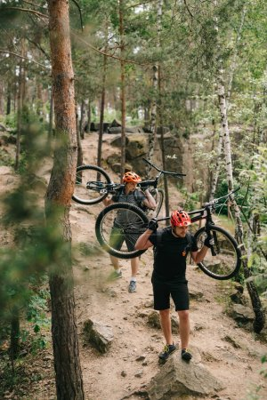young trial bikers carrying bikes on backs at forest