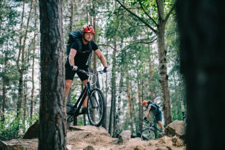 extreme young trial bikers riding at beautiful pine forest