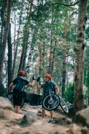 young trial bikers giving high five at beautiful forest