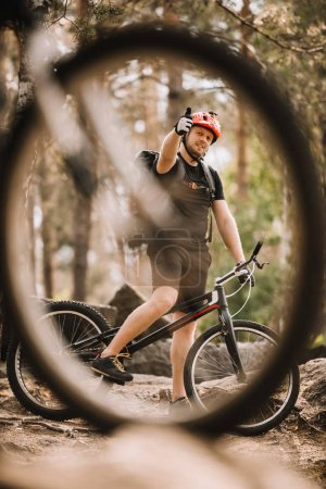 view of young trial biker showing thumb up at forest through bike wheel