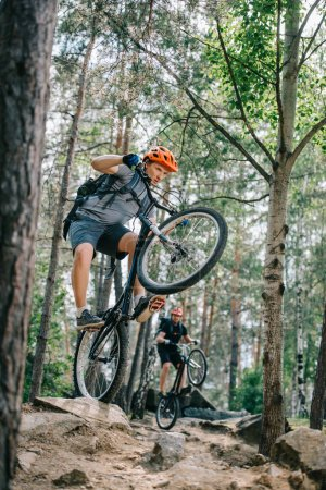 young trial bikers riding on back wheels at beautiful forest