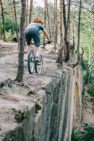 extreme trial biker riding on cliff at forest