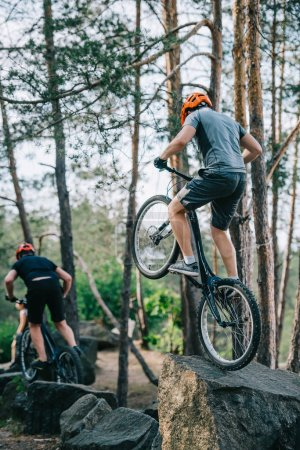 athletic young trial bikers performing stunts on boulders