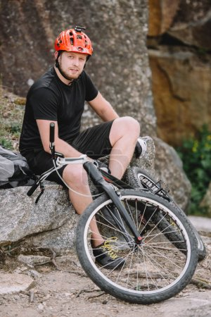 handsome young trial biker relaxing on rocks with bicycle outdoors and looking at camera