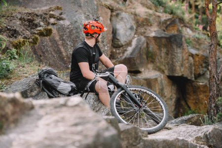 young trial biker relaxing on rocks with bicycle outdoors and looking at away