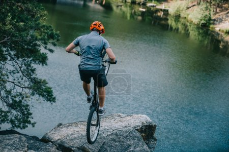 young trial biker balancing on back wheel on rocky cliff over lake