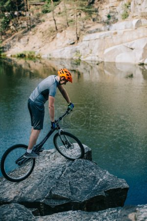 athletic trial biker balancing on rocky cliff over lake