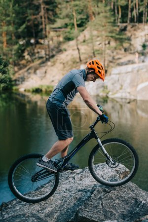 young trial biker balancing on rocky cliff over lake