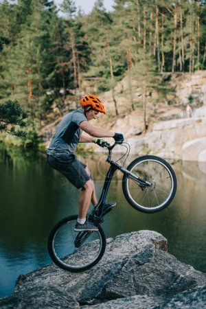 athletic trial biker balancing on back wheel on rocky cliff over lake