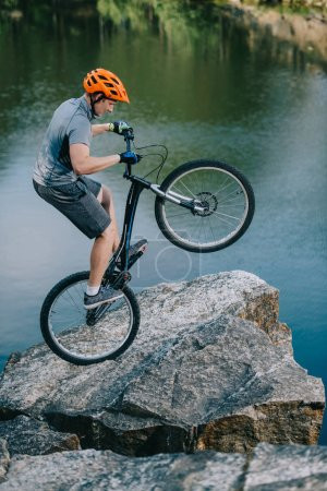 extreme trial biker balancing on back wheel on rocky cliff over lake