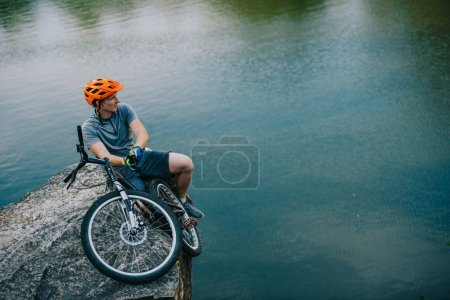 handsome young trial biker relaxing on rocky cliff over water