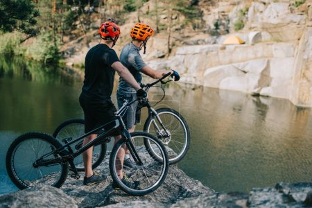 extreme trial bikers standing on rocky cliff in front of mountain lake