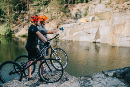 Photo for Young trial bikers standing on rocky cliff in front of mountain lake and pointing at side - Royalty Free Image