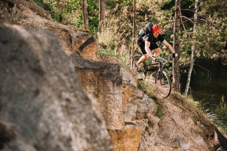 Photo pour Jeune motard du procès d'équitation en descente à l'extérieur dans la forêt de pins - image libre de droit