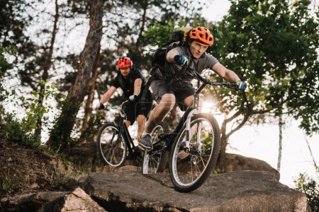 athletic young trial bikers riding on rocks at pine forest