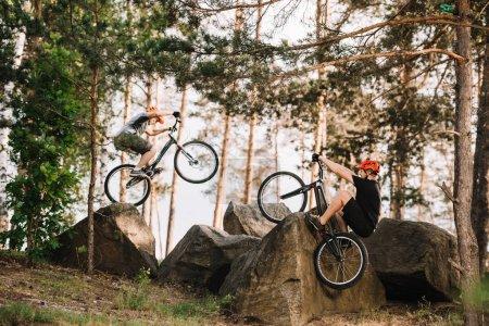 Photo pour Des motards d'essai actifs effectuant des cascades sur des rochers à l'extérieur - image libre de droit